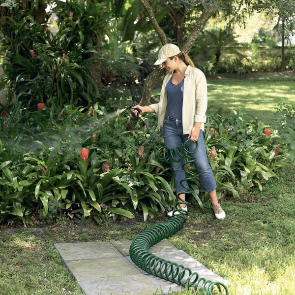 Woman Using Coiled Garden Water Hose